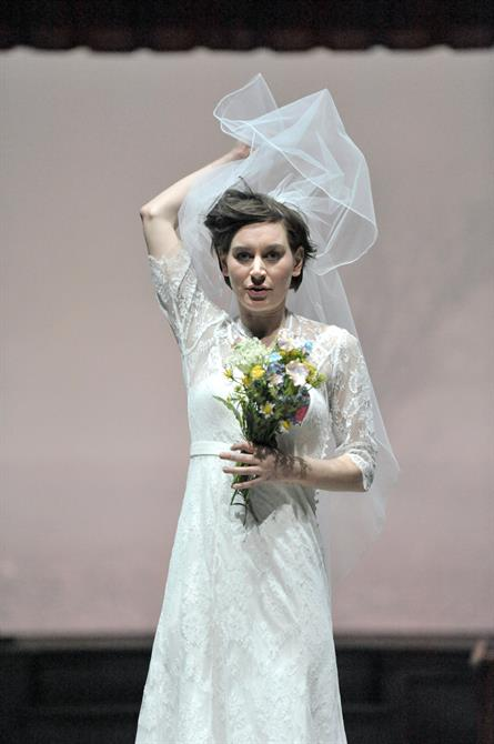 Pippa Nixon as Ophelia wearing a wedding dress, lifting her veil up with one hand