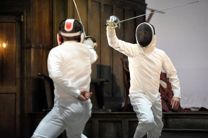 Jonathan Slinger as Hamlet and Luke Norris as Laertes sword fighting dressed in white fencing costumes with black visors