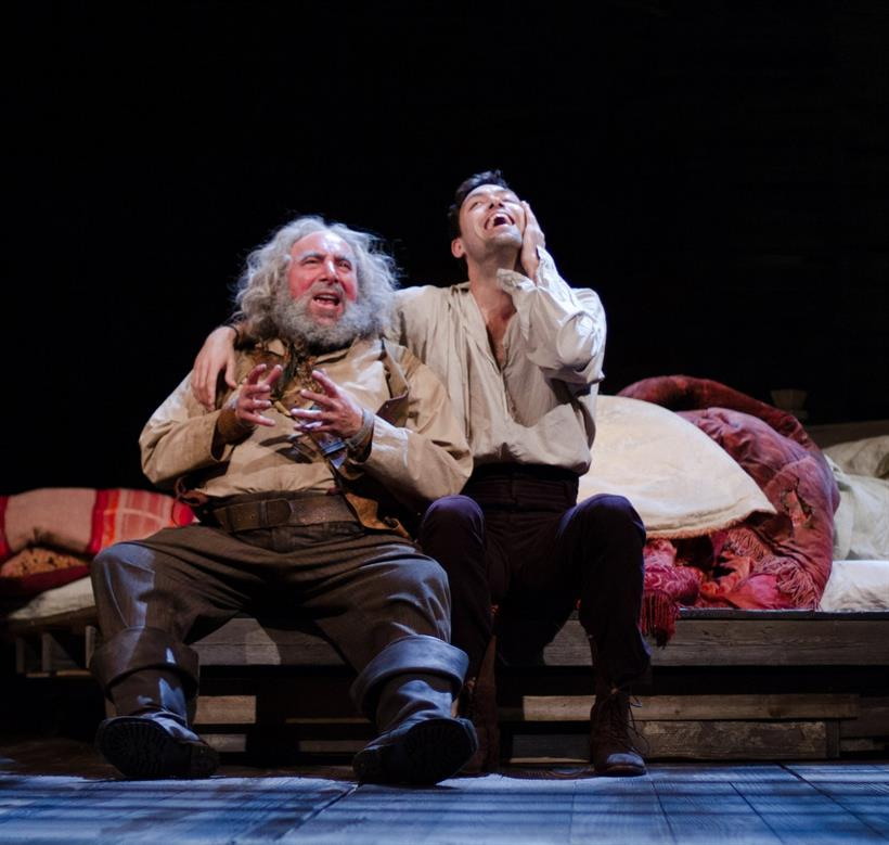 Antony Sher as Falstaff, wearing a light brown shirt and leather boots, chatting with Prince Hal (Alex Hassell), both sitting on a bed