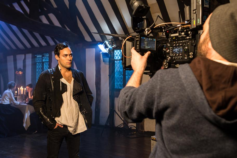 Alex Hassell as Prince Hal stands before a camera in a dimly lit cottage