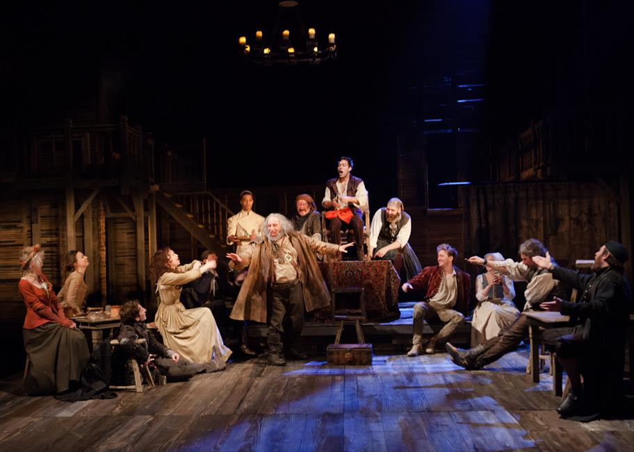 The company of Henry IV Part I in a pub setting, everyone wearing period costumes. Hal sits on a fake throne while Falstaff gestures