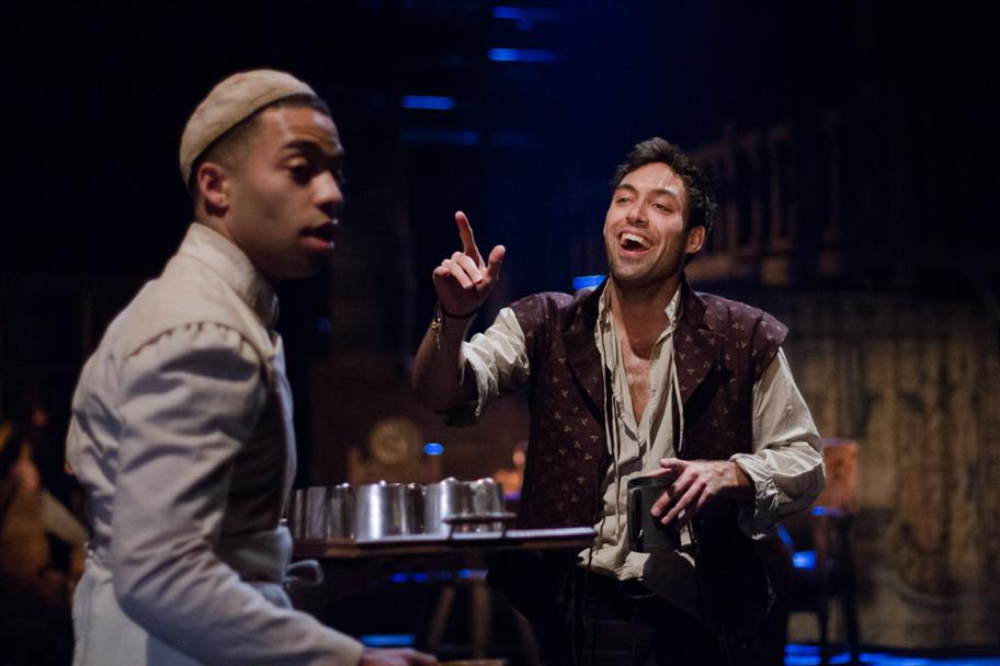 Elliot Barnes-Worrell holding a tray of drinks while Alex Hassall as Prince Hal laughs