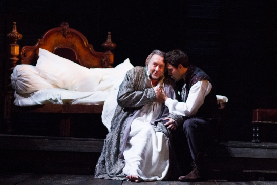 Jasper Britton as King Henry IV and Alex Hassell as Prince Hal, sitting together on the edge of a bed