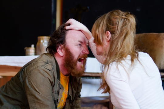 A woman holds a screaming man by the hair.