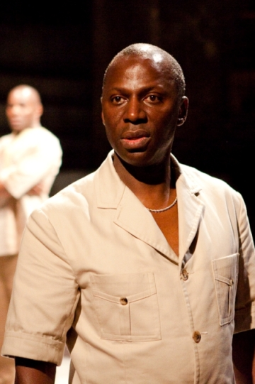 A man in a white shirt and necklace faces away the audience while being watched by another man behind.