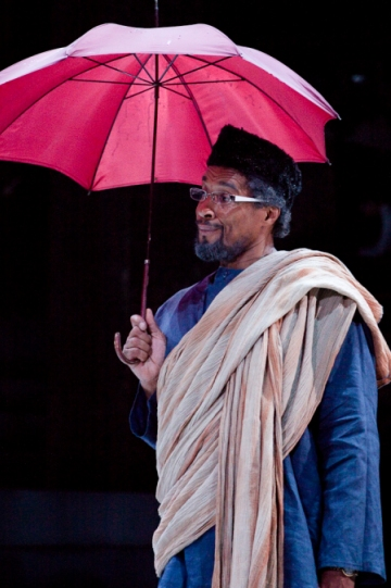 A man in a blue shirt with a white shawl carries a red umbrella.