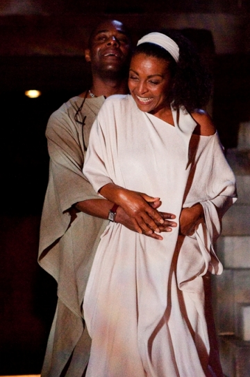 A man in a grey robe puts his arms around a smiling woman in a white robe.