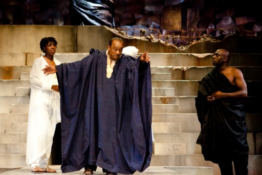 A man in a large blue robe holds his hands out as a man and woman look on.