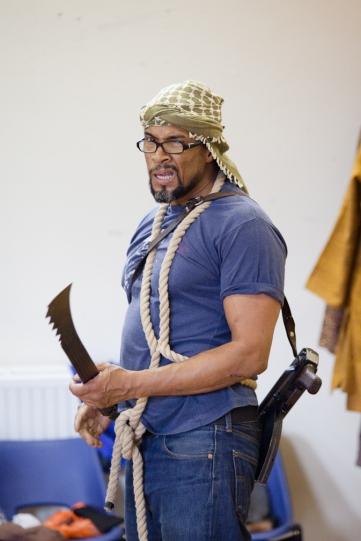 Ricky Fearon carries a machete and a gun in rehearsal for Julius Caesar.
