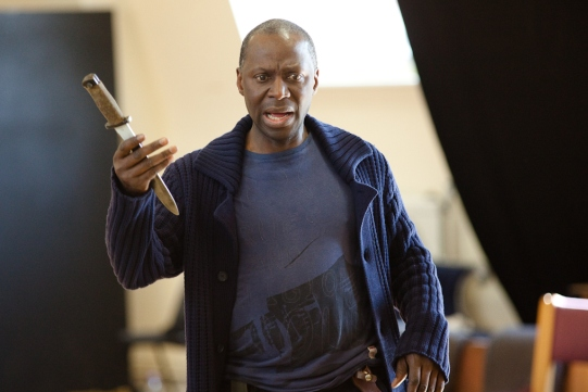 Cyril Nri holds a dagger in rehearsal for Julius Caesar.