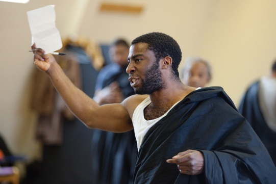 Mark Ebulue brandishes a piece of paper in rehearsal for Julius Caesar.