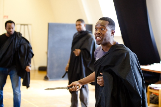 Segun Akingbola holds out a knife in rehearsal for Julius Caesar.