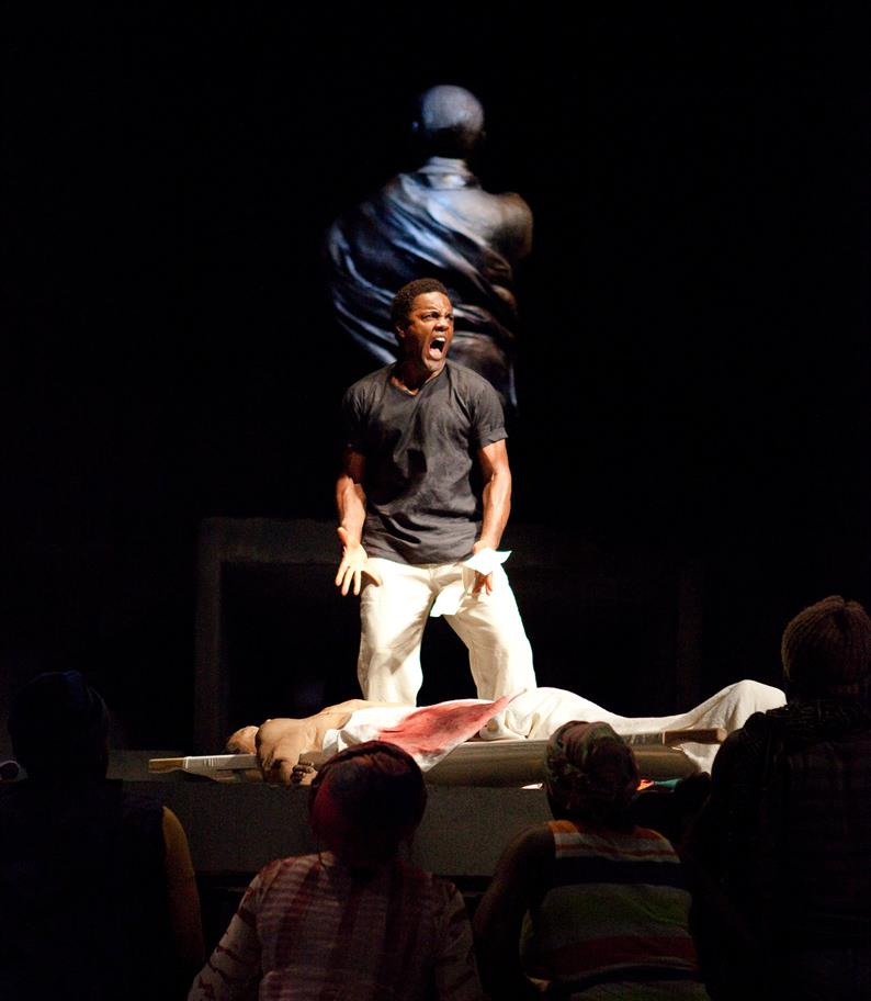 Ray Fearon as Mark Antony kneels on stage, shouting as a body lies in front of him.