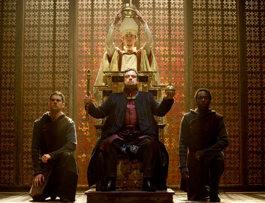 A king is crowned on his throne as he holds a sceptre and ball aloft.