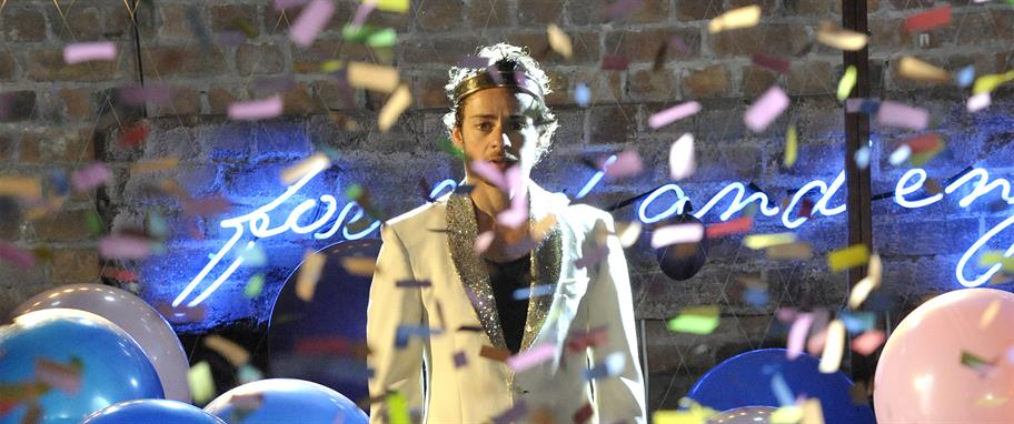 Alex Waldmann as King John, wearing a sparkling white suit and standing among balloons and confetti
