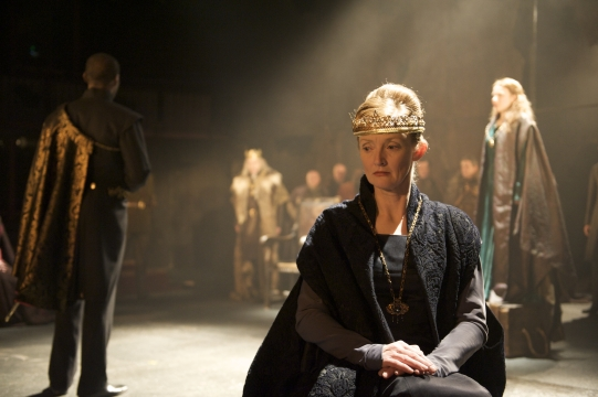Dressed in her regal finery, Goneril (foreground, Kelly Hunter) listens as Cordelia (background, Samantha Young) angers their father.