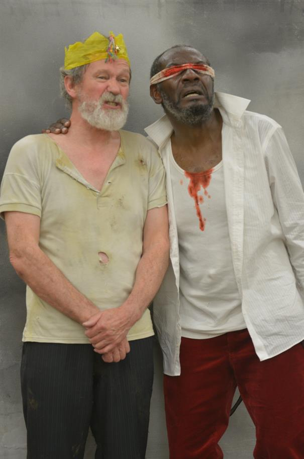 Two men, one with a bloodied bandage around his eyes