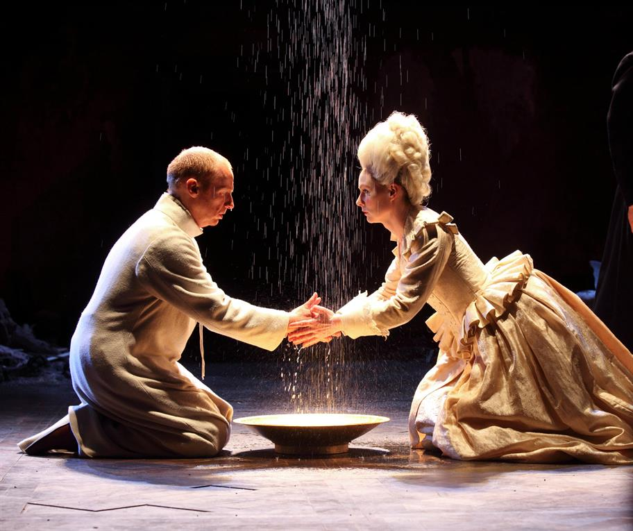 A man and a woman in Elizabethan outfits kneel before a plate, into which sand is falling