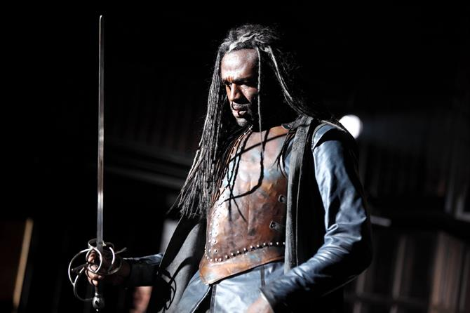 Steve Toussaint with a sword on the RSC stage performing in Macbeth.