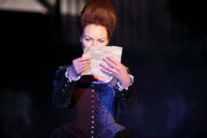 Aislin McGuckin on the RSC stage in costume performing in Macbeth, reading a letter.