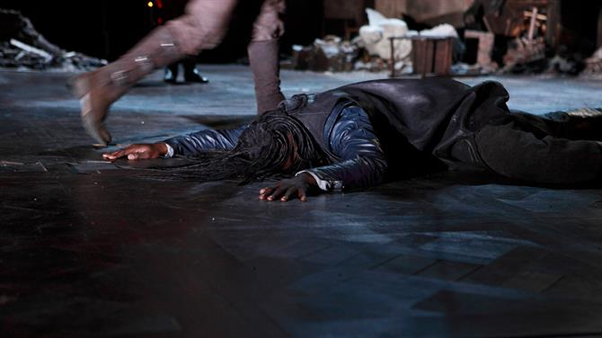 A man in a dark leather suit lying face down on the floor