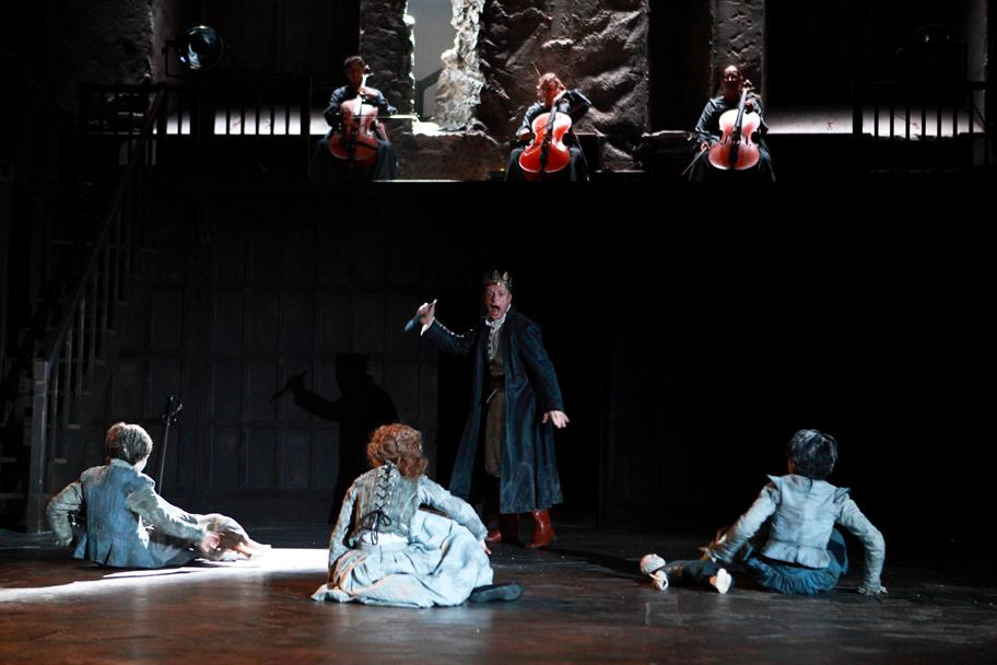 Three children sit with their back to the stage as a crowned figure approaches them with a weapon and three cellists play in a gallery above