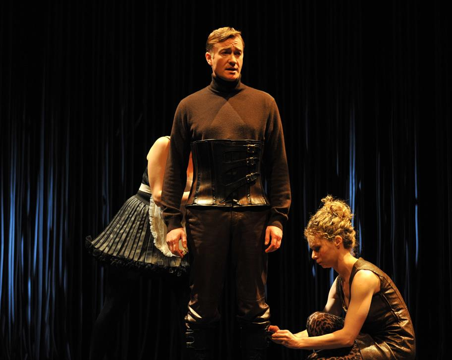 A man stands, centre, wearing a leather corset, while two women dress him.