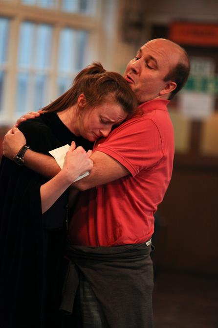 Jodie McNee (left) and Paul Chahidi (right) embracing in rehearsal for Measure for Measure.