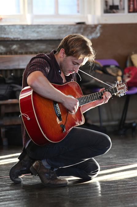 Sam Marks playing the guitar in rehearsal for Measure for Measure.