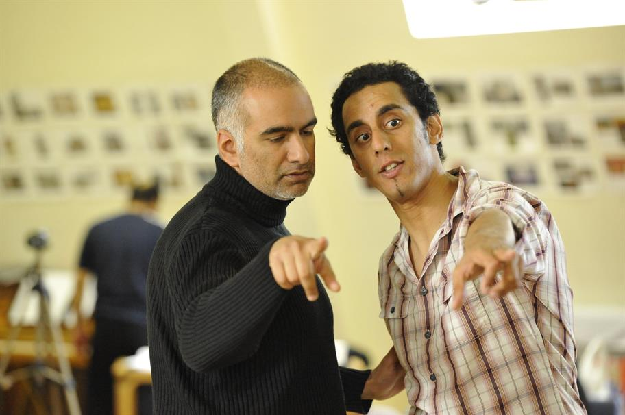 Director Iqbal Khan wearing a black turtleneck, working with an actor