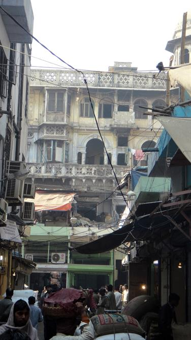 A bustling overcrowded street in Old Dehli, India, with overhanging galleried buildings.