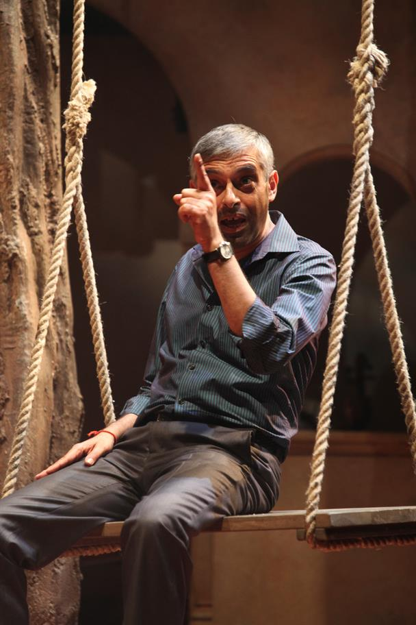 Paul Bhattacharjee sitting on a swing and pointing his finger as Benedick