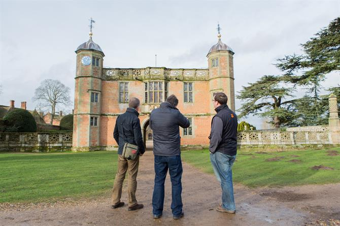 Three men stand outside Charlecote Park, a stately home