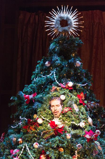 A man's face peers out from the middle of a decorated Christmas tree