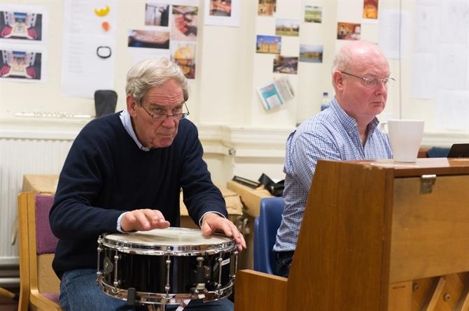 John Woolf and Nigel Hess in rehearsals, one on a drum and the other behind a piano