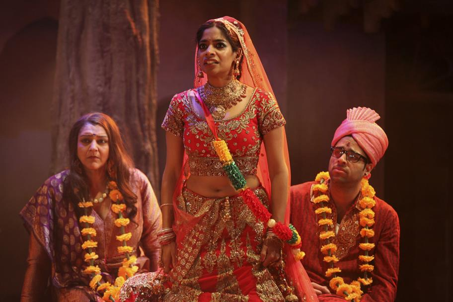 Meera Syal as Beatrice, in a red dress and wearing a flower wreath; Amara Karan as Hero, in a traditional red Indian wedding dress