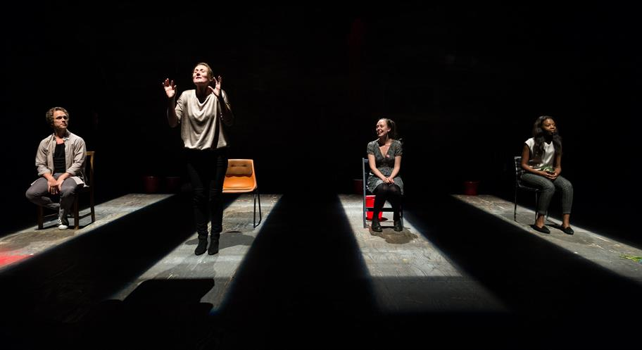 Three people sit on chairs in thin bars of light. A woman stands with her arms held up.