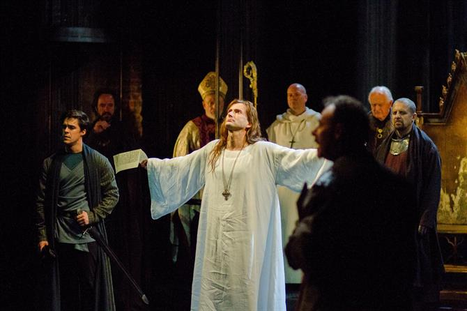 Bolingbroke's court witness Richard II (David Tennant), dressed simply in a white shift and wearing a crucifix, reluctantly resign his crown