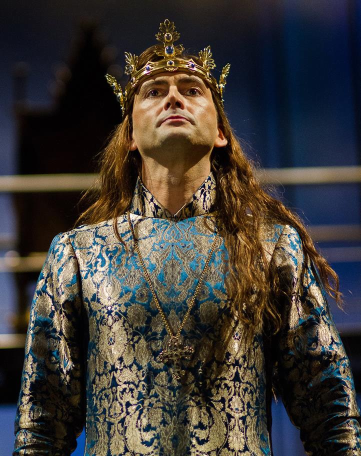 David Tennant as Richard II, in an ornate blue and gold robe, wearing a golden cross and gemmed crown.