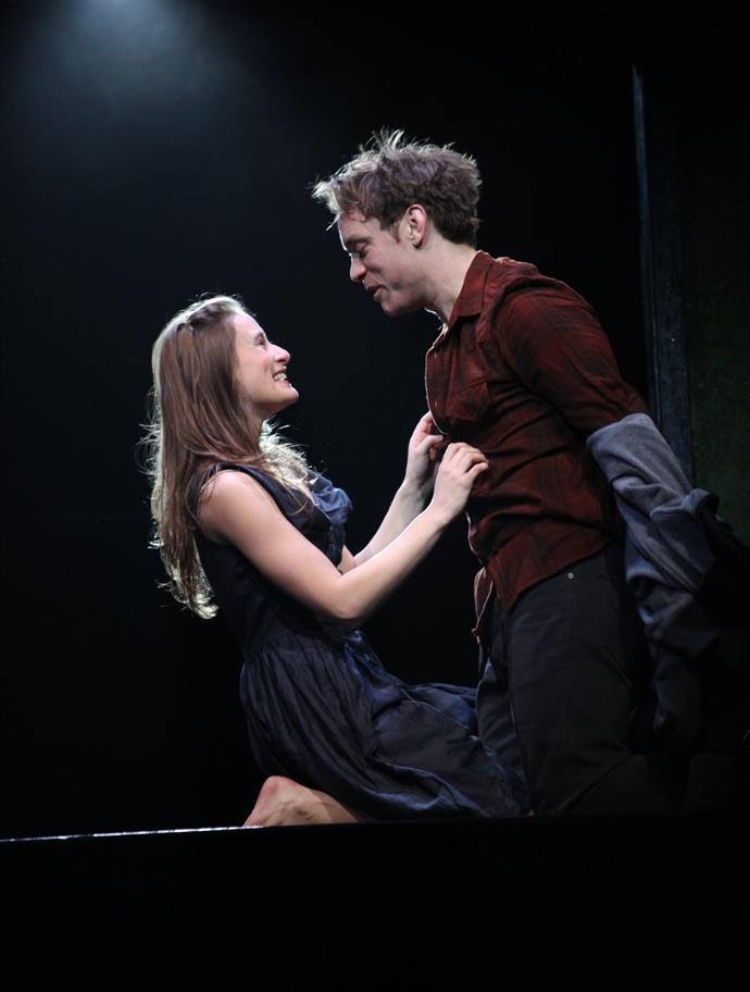A modern-dressed laughing young woman starts to undress a young man