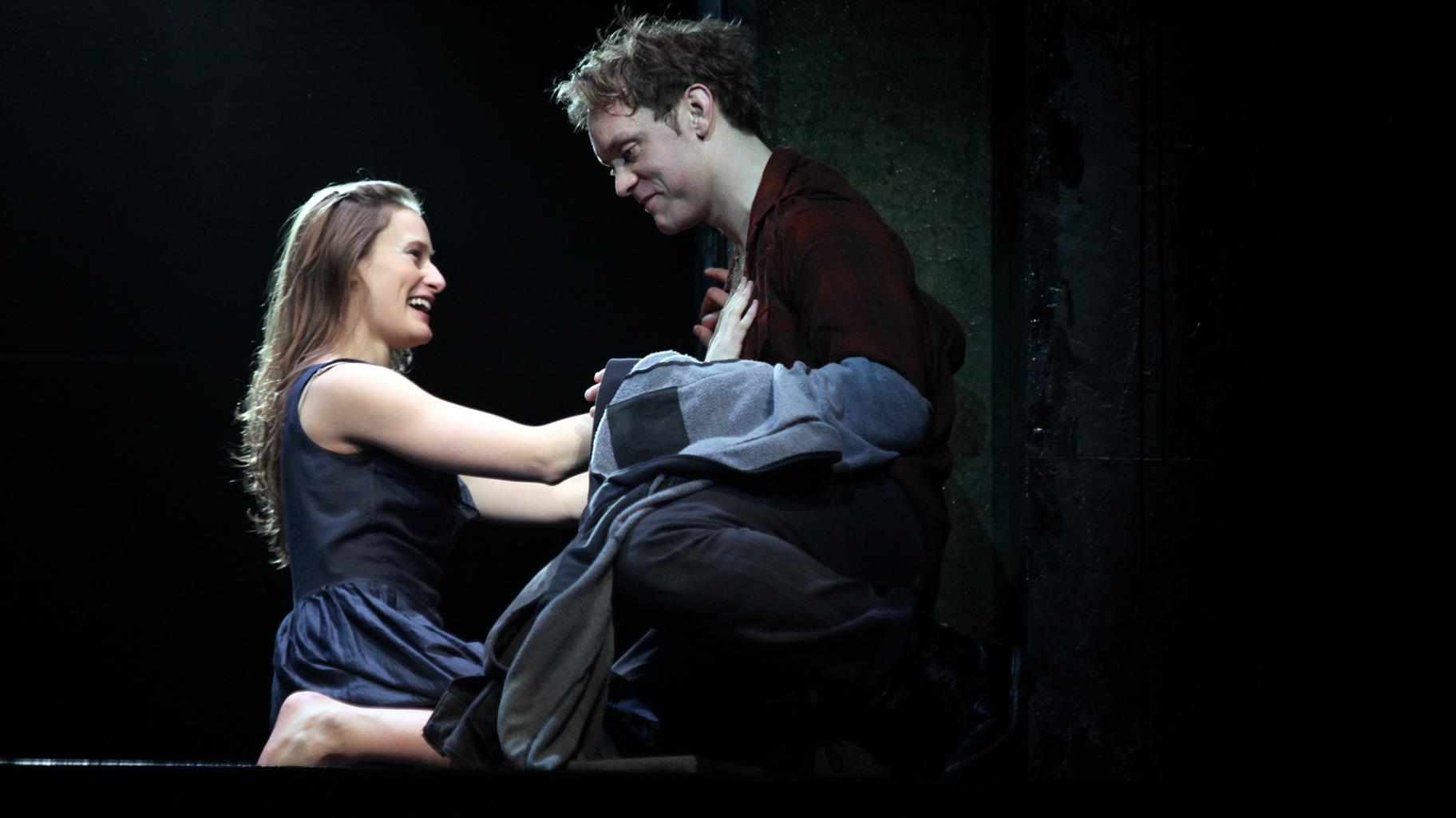 Mariah Gale as Juliet , touching Romeo (Sam Troughton) on his chest, smiling