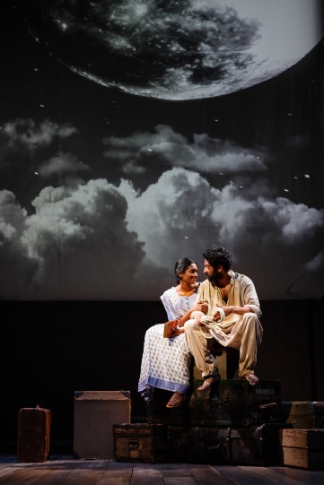 A man and woman sit together under an image of the moon