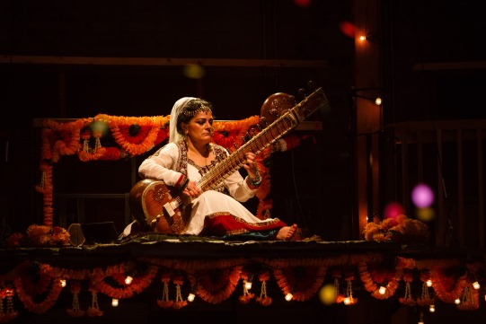 A woman in white sits on stage playing a sitar