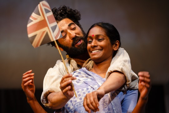 Ray Panthaki as Hari and Anneika Rose as Rani in The Empress, waving a Union flag