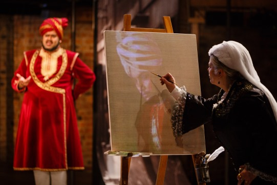 A woman paints a portrait of a man in red robes