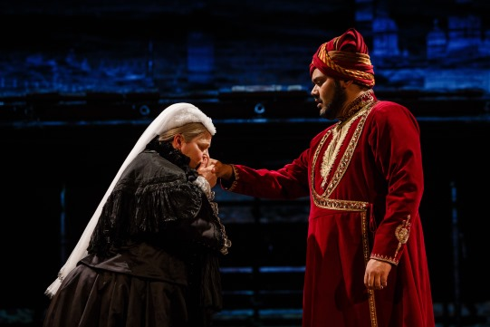 A woman kisses the hand of a man in red robes and turban