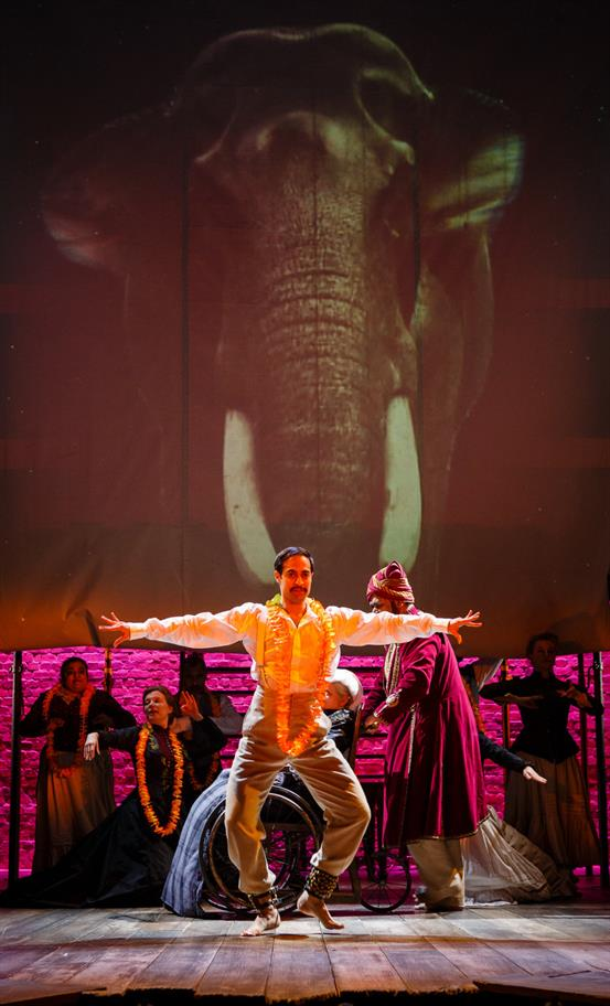 Man dancing wearing a garland around his neck and in front of a giant projected image of an elephant