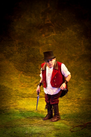 Michael Walter, wearing a red waistcoat and top hat, carries a dagger.