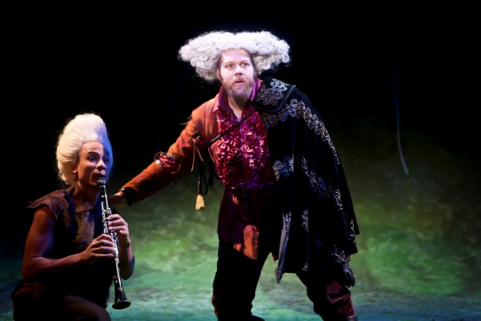 A man playing a clarinet kneels beside a man with a white wig sticking out on the top of his head