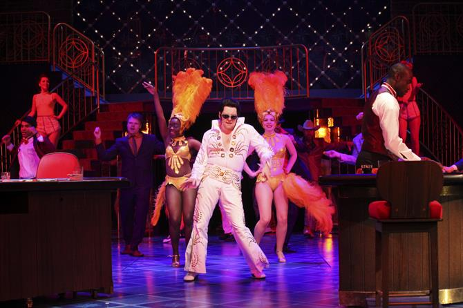 An Elvis impersonator in a white Vegas-style suit with cabaret dancers.